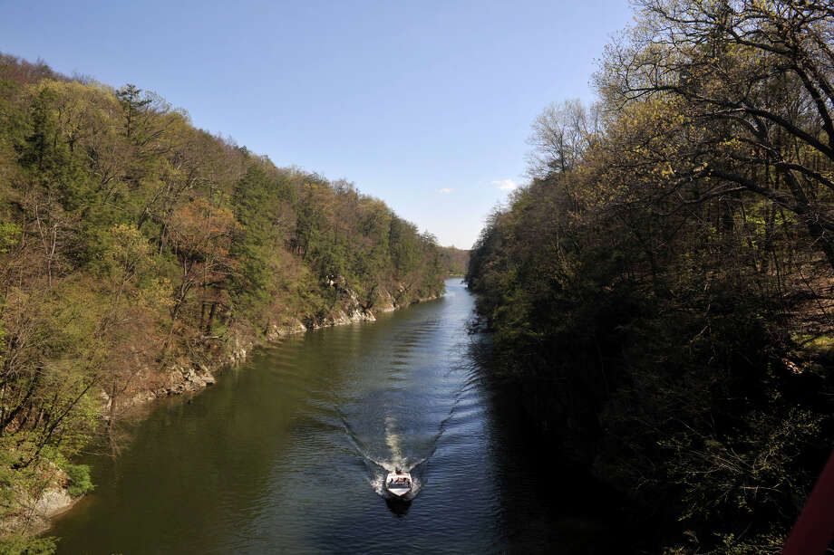 A boat floats down the gorge in Lake Lillinonah near Lovers Leap State Park in New Milford on Thursday, April 19, 2012. The state wants to reduce algae growth in Lake Lillinonah by requiring Danbury to upgrade the city's sewage system, which would limit the release of phosphorus into the lake. Phosphorus is an integral chemical in plant and algae growth. Photo: Jason Rearick / The News-Times