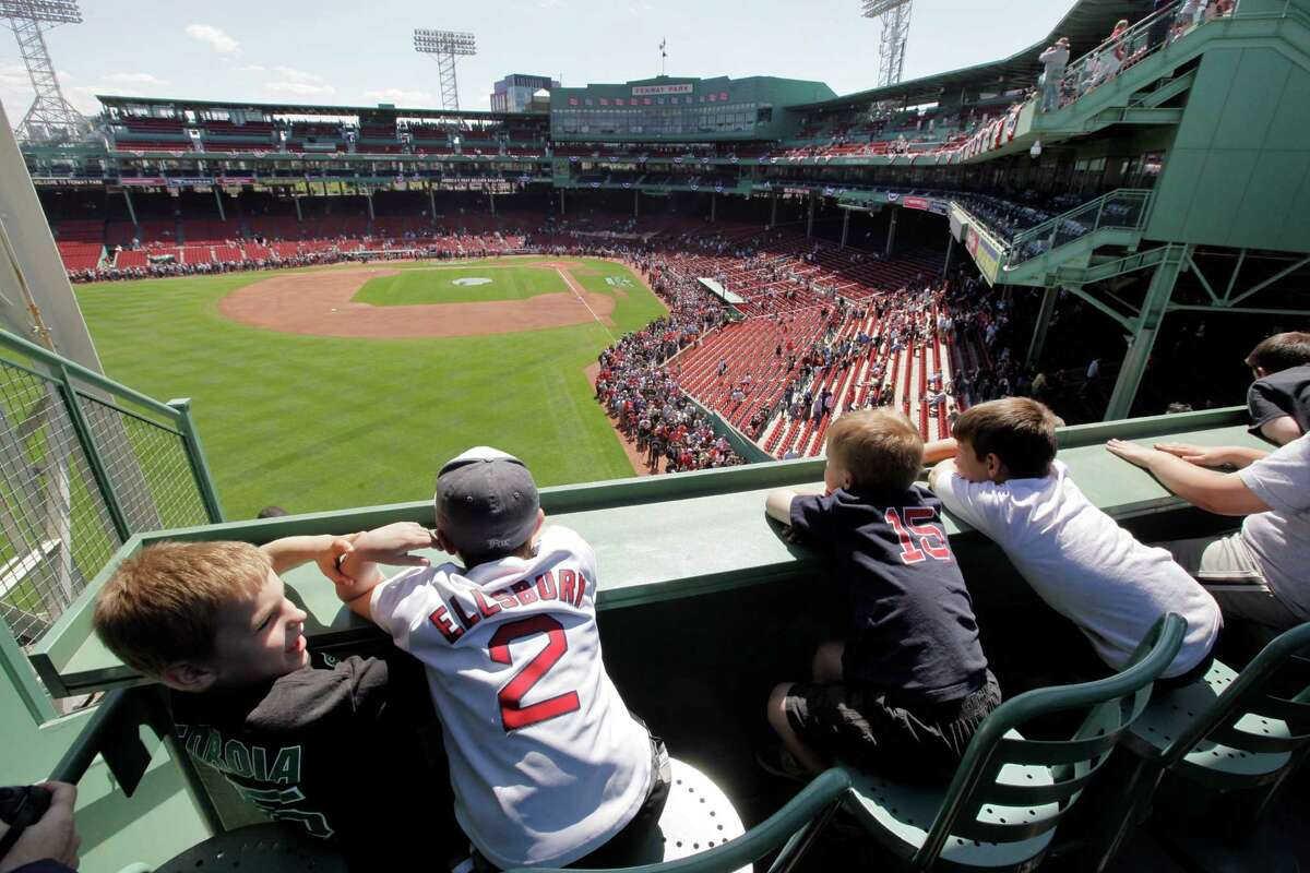 Youngsters sit in and look out from the Green Monster seats during