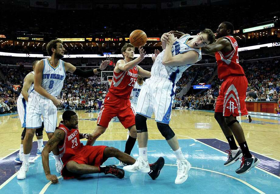 New Orleans Hornets power forward Jason Smith, second from right, tries to pull in a loose ball as Houston Rockets center Marcus Camby (29) falls to the court in the first half of an NBA basketball game in New Orleans, Thursday, April 19, 2012. (AP Photo/Gerald Herbert) Photo: Gerald Herbert, Associated Press / AP