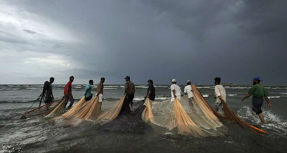 Pakistani fishermen drag their nets for fishing as heavy clouds gather in Karachi, Pakistan, Thursday, April 19, 2012. (AP Photo) Photo: Uncredited, Associated Press