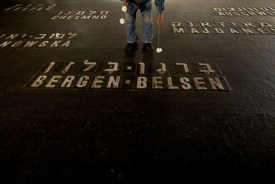 A Holocaust survivor lays flowers next to the names of concentration camps during the annual ceremony on Holocaust Remembrance Day at the Yad Vashem memorial in Jerusalem, Thursday, April 19, 2012. Israel is marking its annual remembrance day for the six million Jews killed by the Nazis in World War II. Photo: Ariel Schalit, Associated Press