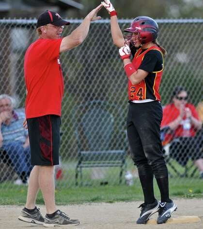 Mechanicville shortstop Alysa Russell celebrates at third base with head coach Don Arceneaux after she hit a triple to drive in two runs, during their victory over Schalmont on Thursday April 19, 2012 in Mechanicville, NY.  (Philip Kamrass / Times Union ) Photo: Philip Kamrass / 00017289A