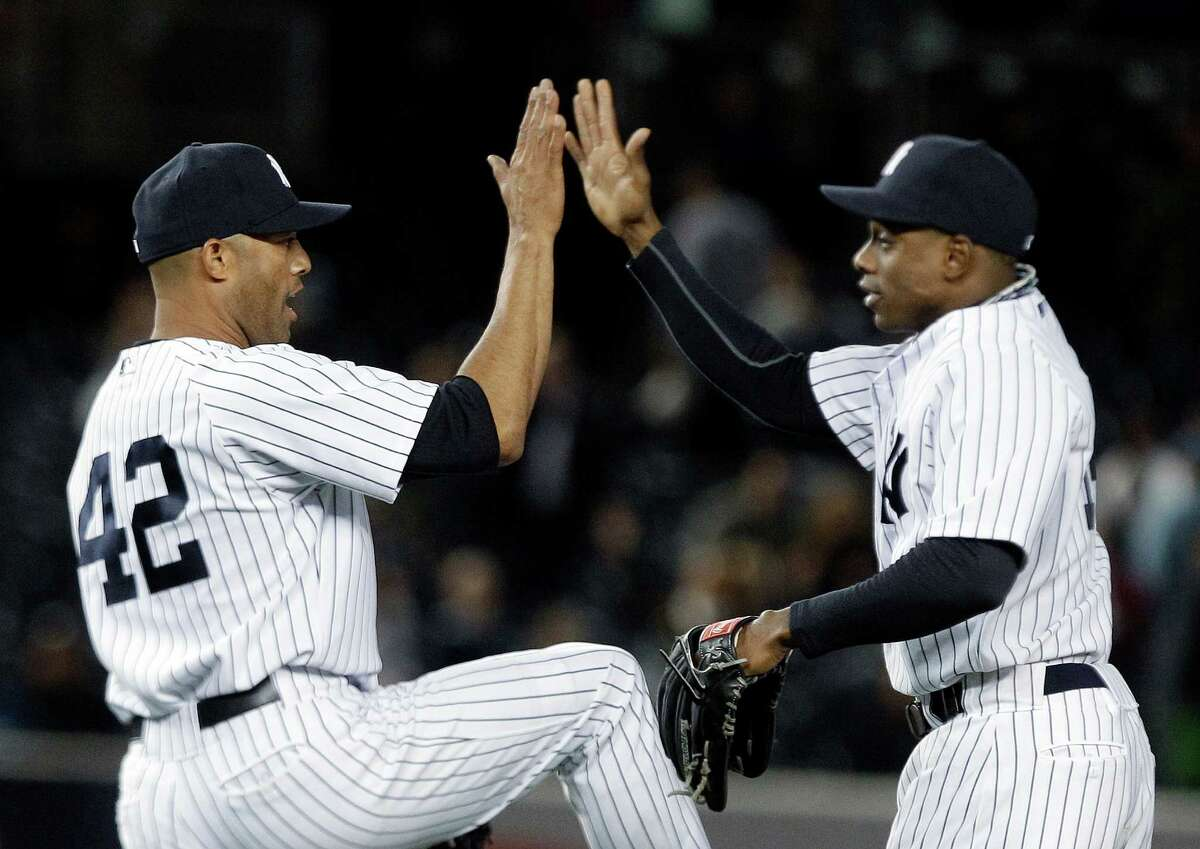 New York Yankees relief pitcher Mariano Rivera, left, and teammate Curtis Granderson celebrate after a baseball game against the Minnesota Twins at Yankee Stadium, Thursday, April 19, 2012, in New York. The Yankees won 7-6. (AP Photo/Frank Franklin II)