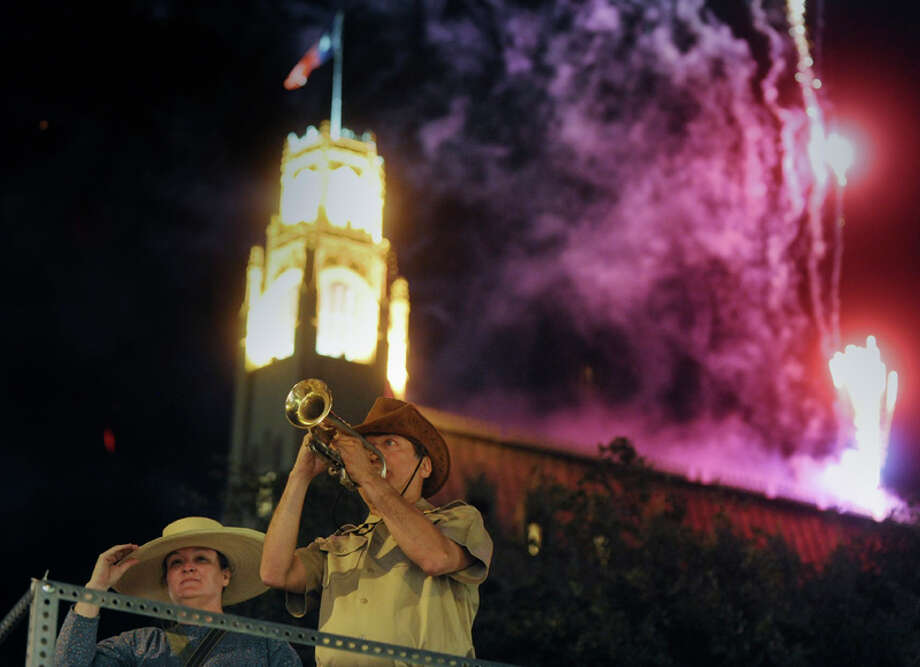 "Sherri Driscoll accompanies Al Gomez , who plays Reveille on coronet, during the opening ceremony for Fiesta 2012 in Alamo Plaza as fireworks go off over the Emily Morgan Hotel on April 19, 2012. Gomez said that it's a wake up call. ""Wake up, it's Fiesta time,"" he said. Photo: BILLY CALZADA,  Billy Calzada / San Antonio Express-News / San Antonio Express-News"