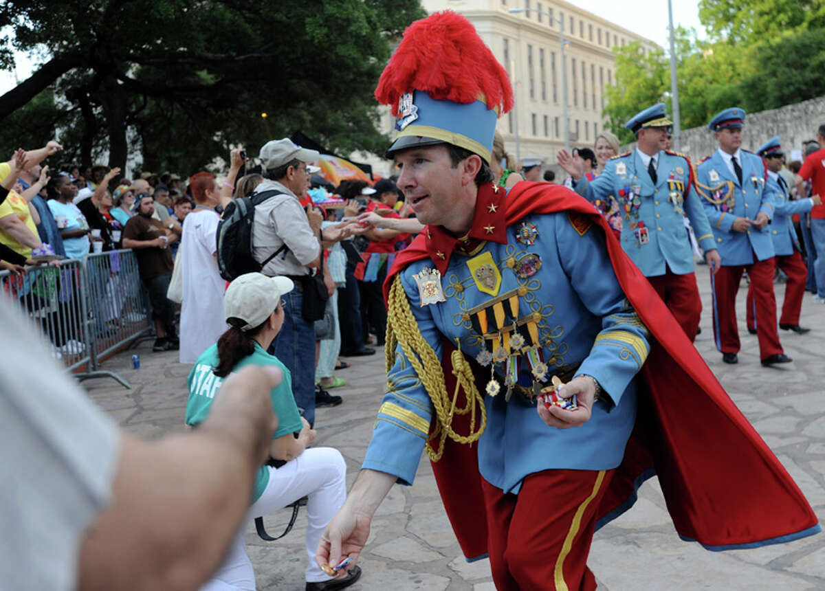 King Antonio XC, Thomas M. Green, tosses medals into the crowd during Fiesta 2012 opening festivities in Alamo Plaza on April 19, 2012.