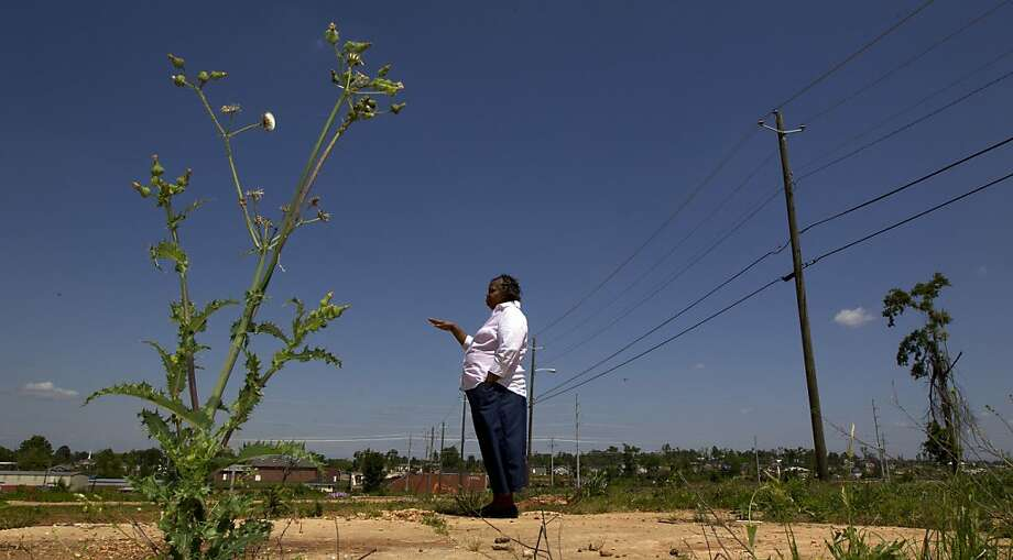 """Sharon Horn, 53, stands on the empty weedy lot in Tuscaloosa, Ala., on Tuesday, April 10, 2012 where her old house stood, Horn described herself as homeless. """"I think when you don't have your own key to unlock your door to go into a place and say 'It's mine,' whether you're renting or own, you're homeless,"""" she said. Horn, 53, was renting a three-bedroom, one-bath home in Tuscaloosa until a massive twister splintered the old house and scattered her possessions across the neighborhood, leaving her with virtually nothing. Her $4,000 in federal disaster aid long gone, Horn now shuttles back and forth between a cousin and a daughter with no place of her own. (AP Photo/Dave Martin) Photo: Dave Martin, Associated Press"""
