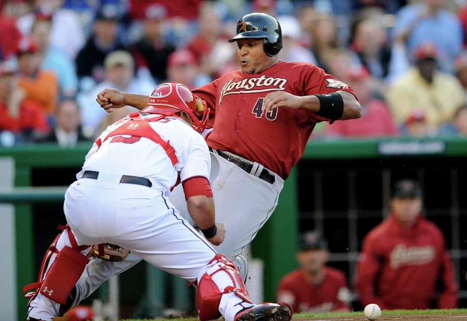 Carlos Lee beats the throw to Nationals catcher Wilson Ramos to score on Brian Bogusevic's triple, one of three triples by the Astros in the first inning. Photo: Nick Wass / FR67404 AP