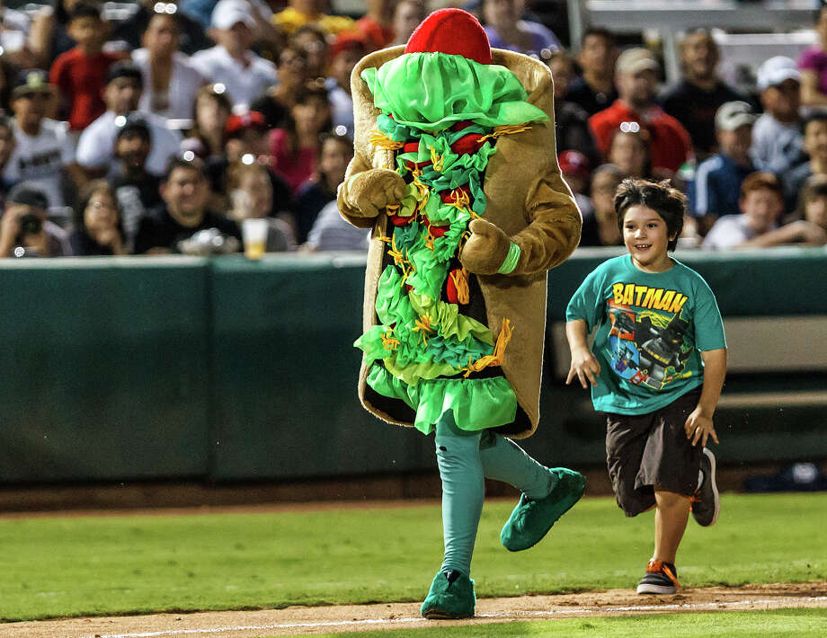 A young fan chases down the Puffy Taco as he heads towards home plate during the Missions game against the Midland RockHounds at Wolff Stadium on Thursday, April 19, 2012. Photo: Marvin Pfeiffer, San Antonio Express-News