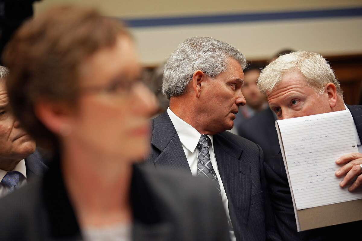 Ex-General Services Administration official Jeffrey Neely (center) talks with his attorney at a hearing.