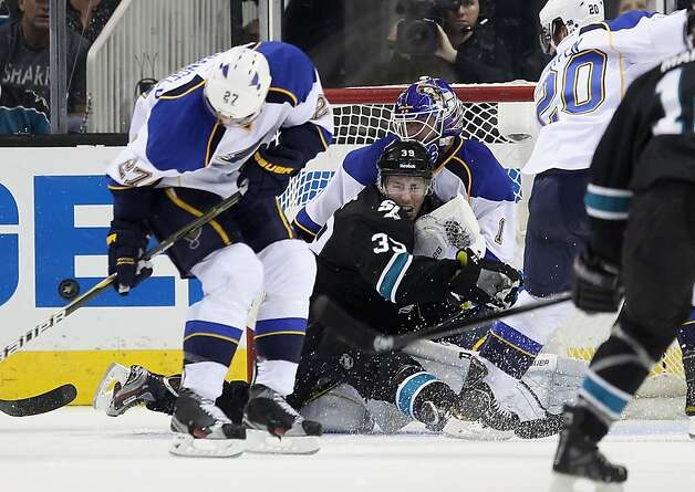 Sharks center Logan Couture (center) ran into Blues goalie Brian Elliott and came out of it the worse for wear. Photo: Ezra Shaw, Getty Images