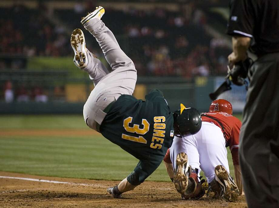 The Oakland Athletics' Jonny Gomes (31) scores over Los Angeles Angels catcher Chris Iannetta in the fourth inning on a throwing error by pitcher C.J. Wilson at Angel Stadium of Anaheim on Thursday, April 19, 2012, in Anaheim, California. (Kevin Sullivan/Orange County Register/MCT) Photo: Kevin Sullivan, McClatchy-Tribune News Service