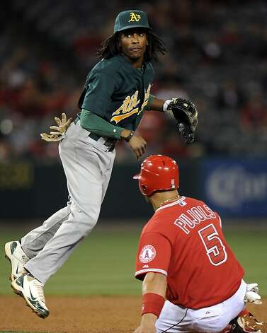Jemile Weeks #19 of the Oakland Athletics throws to first base for a double play to end the game in front of Albert Pujols #5 of the Los Angeles Angels during the ninth inning at Angel Stadium of Anaheim on April 19, 2012 in Anaheim, California.  The A's won 4-2. Photo: Harry How, Getty Images