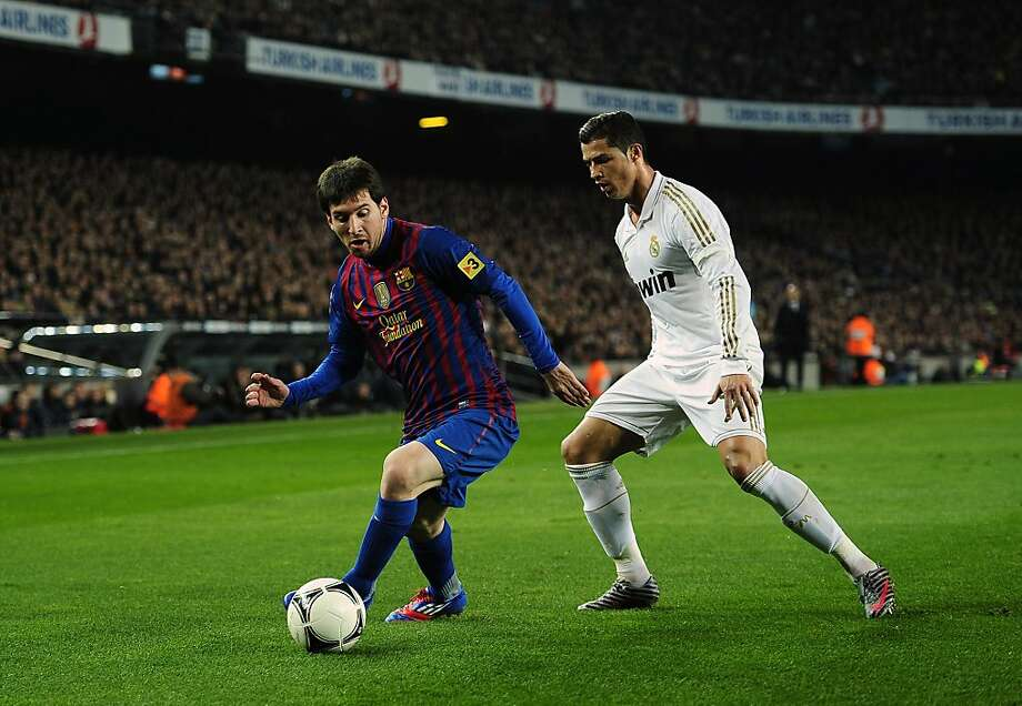 FILE - In this Jan. 25, 2012 file photo FC Barcelona's Lionel Messi from Argentina, left, duels for the ball with Real Madrid's Cristiano Ronaldo from Portugal, during their quarterfinal, second leg, Copa del Rey soccer match at the Camp Nou stadium, in Barcelona, Spain. Barcelona and Real Madrid lead Spanish football's European dominance, though the league's continental success is masked by a ticking time bomb of heavy debt and poor management which could ultimately end with struggling clubs disappearing altogether. (AP Photo/Manu Fernandez, File) Photo: Manu Fernandez, Associated Press