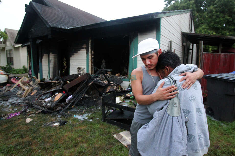 Chenita Patterson,36, (right) is consoled by her neighbor Ted Garcia (wearing cap) after her home at 4021 Indian Sunrise caught on fire about 3:30 a.m. Friday April 20, 2012. Patterson was reacting after finding her pet chihuahua in her next door neighbor's back yard. The dog had shallow breathing and was taken away by a neighbor to get medical attention. Patterson said she thought the fire started from an electrical problem. Photo: JOHN DAVENPORT, SAN ANTONIO EXPRESS-NEWS / SAN ANTONIO EXPRESS-NEWS (Photo can be sold to the public)