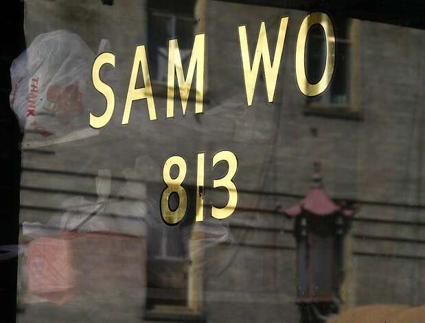 A building on Washington Street is reflected in the front window of Chinatown's legendary Sam Wo restaurant in San Francisco, Calif. on Thursday, April 19, 2012. The restaurant's owner is closing its doors for good on Friday. Photo: Paul Chinn, The Chronicle
