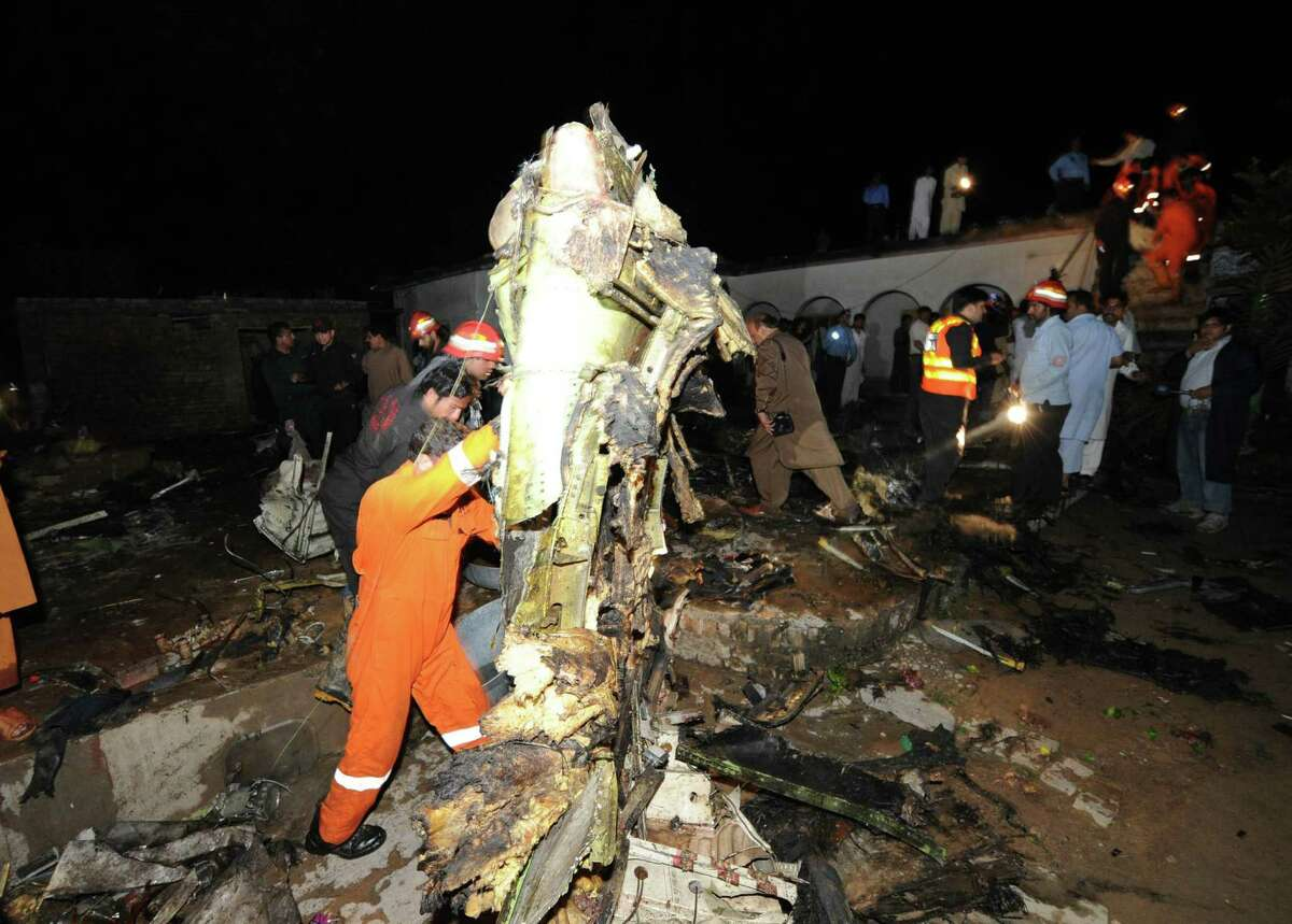 Pakistani rescue workers and local residents search the site of a plane crash in Rawalpindi on Friday. There is