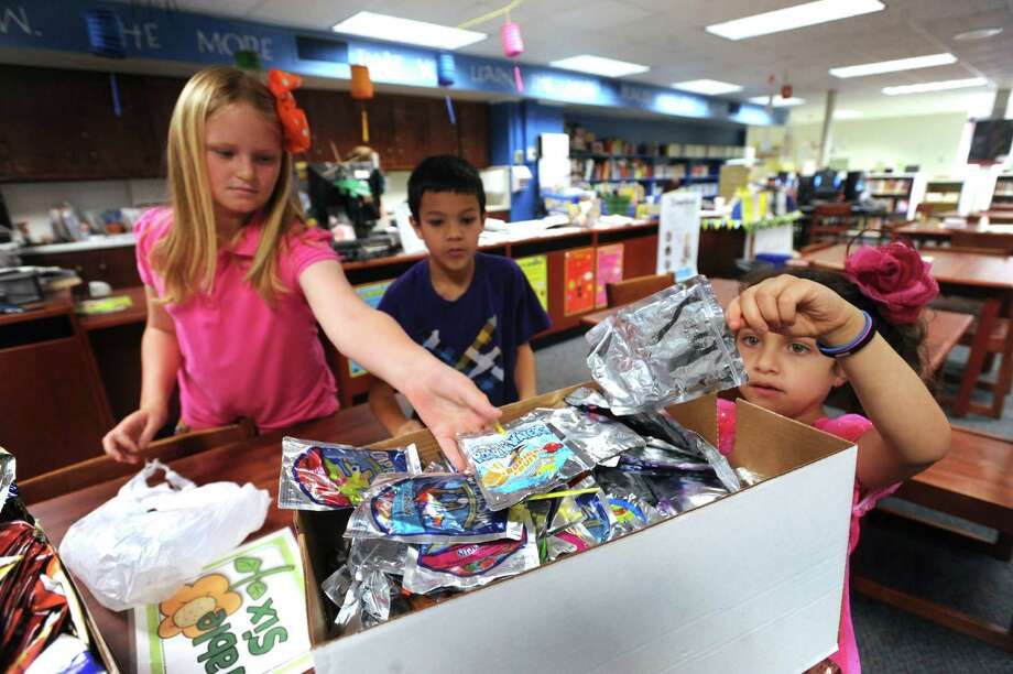 Harmony Hills Elementary fourth-grade students Emily Wissellittmann, left, and Jacob Maes, and kindergarten student Tresbella Rodriguez sort drinking pouches gathered at lunch for recycling. The students participate in the school's TerraCycle recycling program. Photo: BILLY CALZADA, San Antonio Express-News / SAN ANTONIO EXPRESS-NEWS