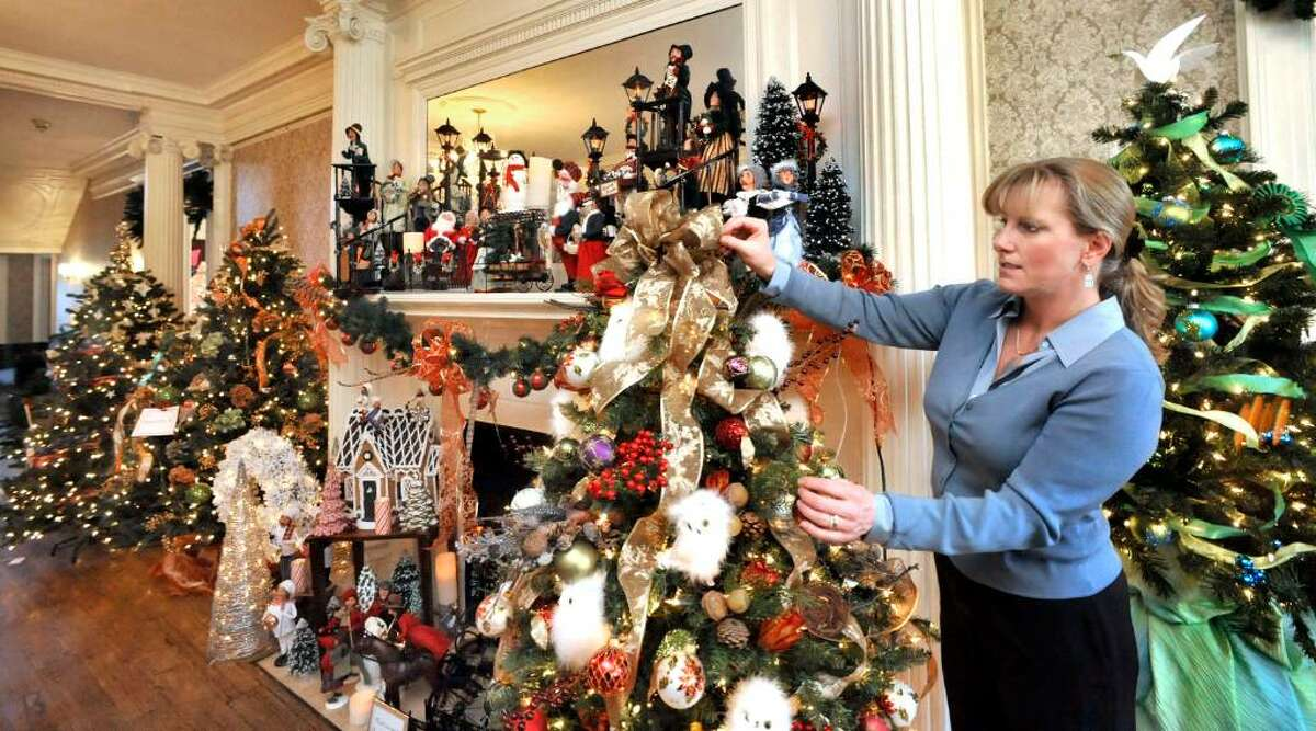 Holly Callanan, Festival Chairman, adjusts a tree in the Ridgefield Community Center, during the Holiday Festival of Trees, on Wendesday,Nov.18,2009.