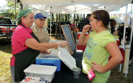Julie Hammond, from left, owner of Hammond Farm, with her mom, Dolores McClere, serves a sample of her Peach Chevre (goat cheese) to customer Addie Trout, 10, a 5th grader at Green Tree Elem., during the Kingwood Farmers Market held at Town Center. Photo: Jerry Baker, For The Chronicle / Freelance