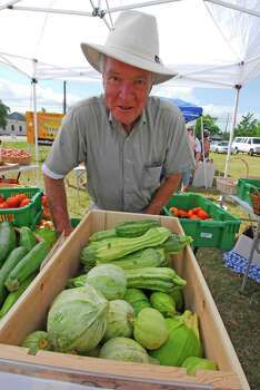 A Farmers Market was held in Tomball Saturday 6/13/09. Bob Ferriman shows zucchini offered for sale by Keatingrove Farms (the only farm in Harris County certified organic by the Texas Department of Agriculture). Photo: Tony Bullard / Freelance