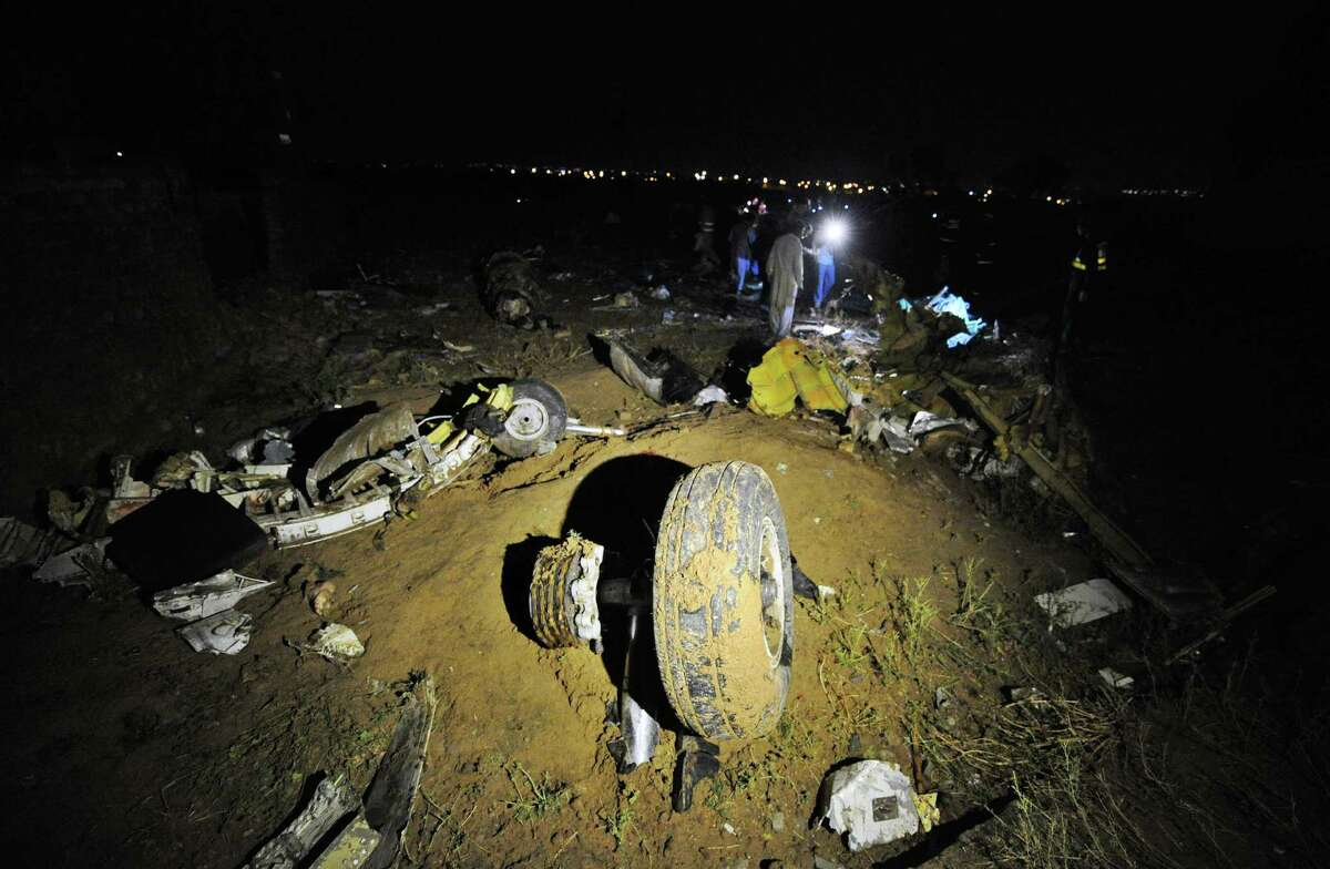 A plane wheel (C) lies amongst debris at the scene of a plane crash as Pakistani rescue workers search for victims in the outskirts of Islamabad on April 20, 2012. Up to 130 people are feared dead after a Boeing 737 crashed while trying to land in bad weather near the Pakistani capital Islamabad on Friday, officials said. The Bhoja Air flight from Karachi came down outside Islamabad's international airport, police official Fazle Akbar said, adding that emergency teams have been sent to the site. AFP PHOTO / AAMIR QURESHI