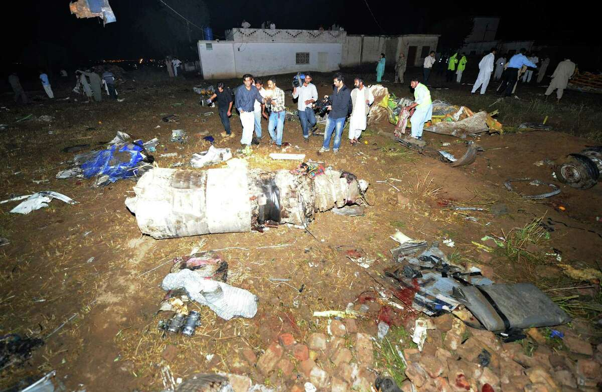 Pakistani rescue workers and media personnel gather at the site of a plane crash in the outskirts of Islamabad on April 20, 2012. Up to 130 people are feared dead after a Boeing 737 crashed while trying to land in bad weather near the Pakistani capital Islamabad on April 20, officials said. The Bhoja Air flight from Karachi came down outside Islamabad's international airport, police official Fazle Akbar said, adding that emergency teams have been sent to the site. AFP PHOTO / AAMIR QURESHI