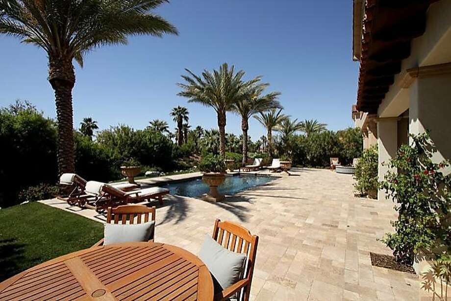A look at the back yard of the property, focusing on the landscaped lawn, palm-lined swimming pool and surrounding patio area. Photo: Photos Courtesy Of Realtor.com