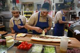 Adrian Hernandes (left) and Ricardo Rosas (middle) making sandwiches, with longtime manager Rafik Zadoorian (right) at the Submarine Center in San Francisco, Calif.,  on Wednesday, April 11, 2012.