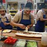 Adrian Hernandes (left) and Ricardo Rosas (middle) making sandwiches, with longtime manager Rafik Zadoorian (right) at the Submarine Center in San Francisco.