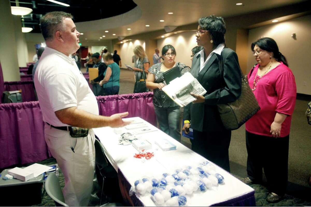 Job seeker Amanda Harris, second from right, talks Tuesday April 17, 2012 at an Express-News/MySA.com-sponsored job fair at the Norris Conference Center at the Wonderland Mall of the Americas to Jeff Dietrich, left, assistant manager of Biotest Pharmaceuticals' local plasma center, about jobs at his company. (William Luther/wluther@express-news.net)