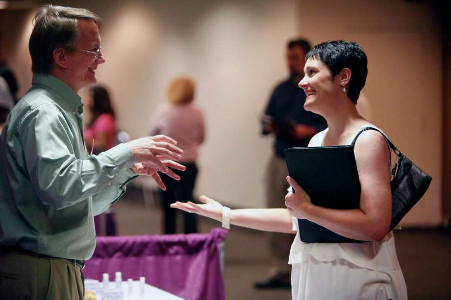 Job seeker Amy Bowles, right, talks Tuesday April 17, 2012 at an Express-News/MySA.com-sponsored job fair at the Norris Conference Center at the Wonderland Mall of the Americas to Biodynamic Research Corporation Human Resource Manager Greg Guetzloe about job oportunities at BRC.   (William Luther/wluther@express-news.net) Photo: William Luther, San Antonio Express-News / © 2012 WILLIAM LUTHER