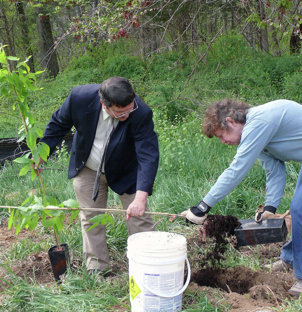 Town Tree Warden Ken Placko and his wife, Cindy Placko, plant American Chestnut trees Friday at the new softball field on Hoydens Lane for Arbor Day.