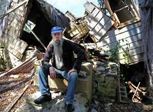 Carl Parker sits in front of what is left of the house he grew up in at 421 Webb Circle in Monroe.  Parker was born in the house and lived there up until town taxes forced him from the property.  Damage from a fire that went unrepaired caused the roof and house to collapse. He spent the last five years living in a camper on his one-acre property.  An obscure state tax abatement statute might have helped Parker keep his property.