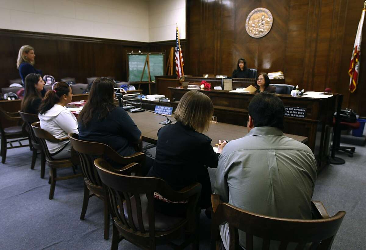 A family appears before Superior Court Judge Gloria Rhynes during a truancy court session at the Alameda County Courthouse in Oakland, Calif. on Friday, June 17, 2011. More than two dozen parents prosecuted for their children's truancy had their cases dismissed after the family completed a program and the students raised their school attendance records.