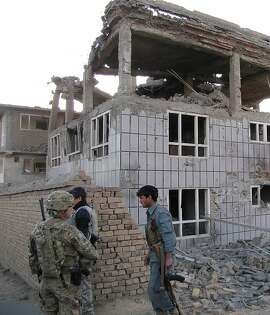 A US soldier (L) and an Afghan policeman (R) stand outside a building which Taliban fighters used to launch an attack in Logar province on April 16, 2012. Afghanistan said its forces regained control of Kabul on April 16, after killing Taliban militants, some disguised as women in burqas, who launched one of the biggest attacks on the capital in a decade of war. AFP PHOTO/Sabawoon Amarkhil (Photo credit should read SABAWOON AMARKHIL/AFP/Getty Images)
