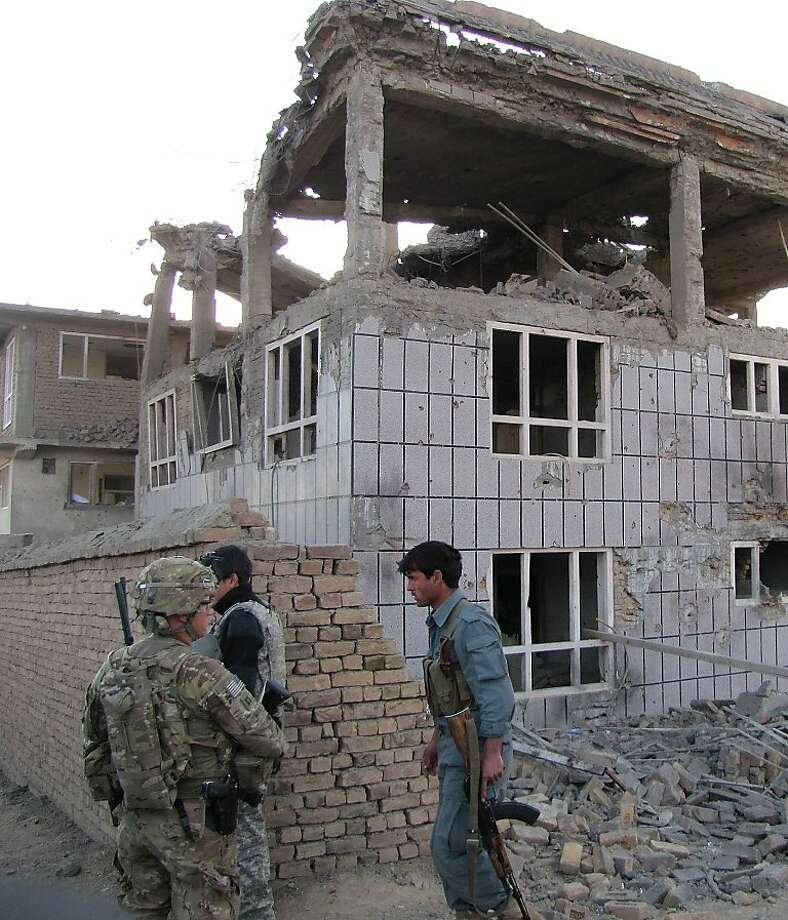 A US soldier (L) and an Afghan policeman (R) stand outside a building which Taliban fighters used to launch an attack in Logar province on April 16, 2012. Afghanistan said its forces regained control of Kabul on April 16, after killing Taliban militants, some disguised as women in burqas, who launched one of the biggest attacks on the capital in a decade of war. AFP PHOTO/Sabawoon Amarkhil (Photo credit should read SABAWOON AMARKHIL/AFP/Getty Images) Photo: Sabawoon Amarkhil, AFP/Getty Images