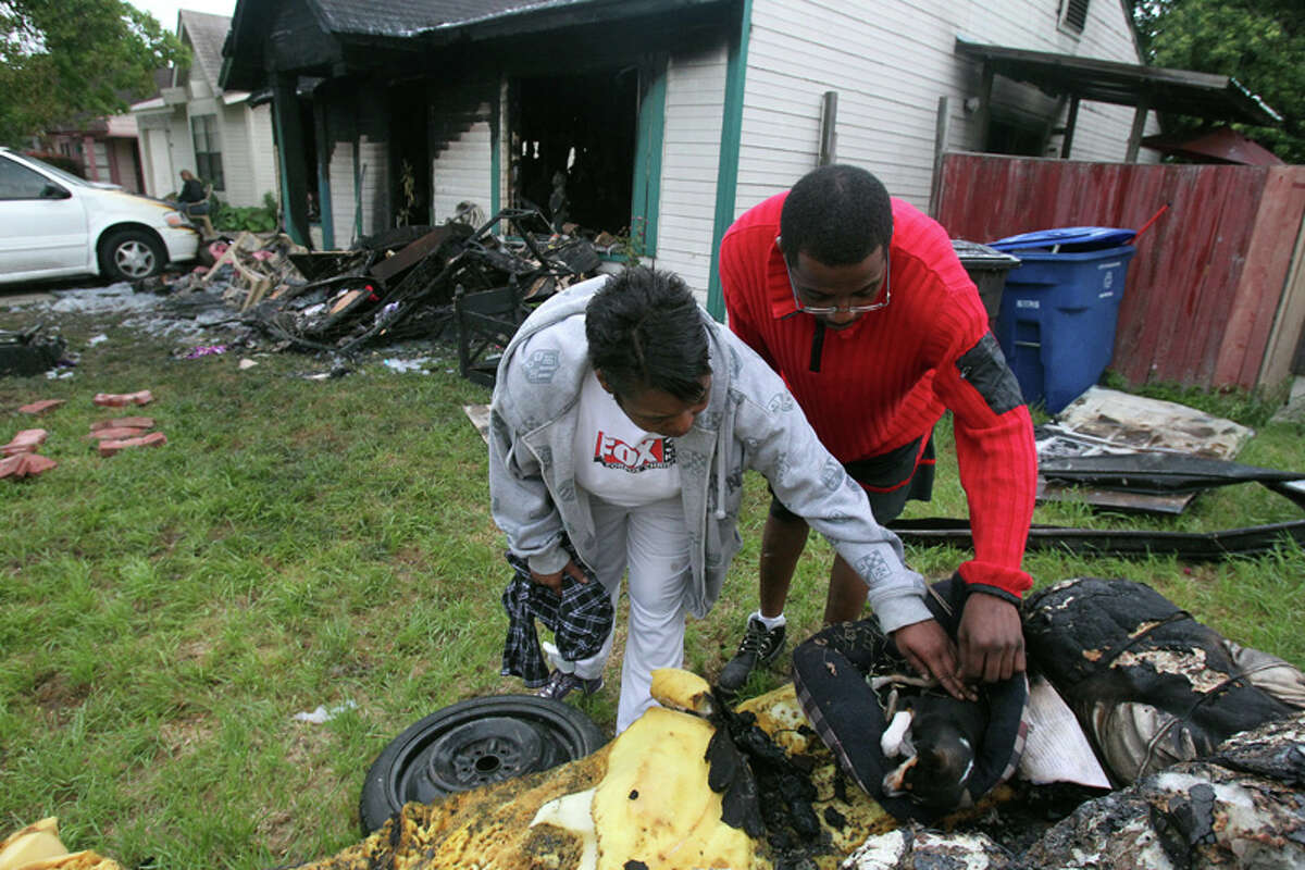 Chanita Patterson (left) and Derrick Deloach (right) check to see if Ceasar the chihuahua is still breathing after Patterson's home burned down early Friday on the 4000 block of Indian Sunrise. The puppy had shallow breathing and was rushed to Kirby Animal Hospital by Deloach. Patterson's home was a total loss.