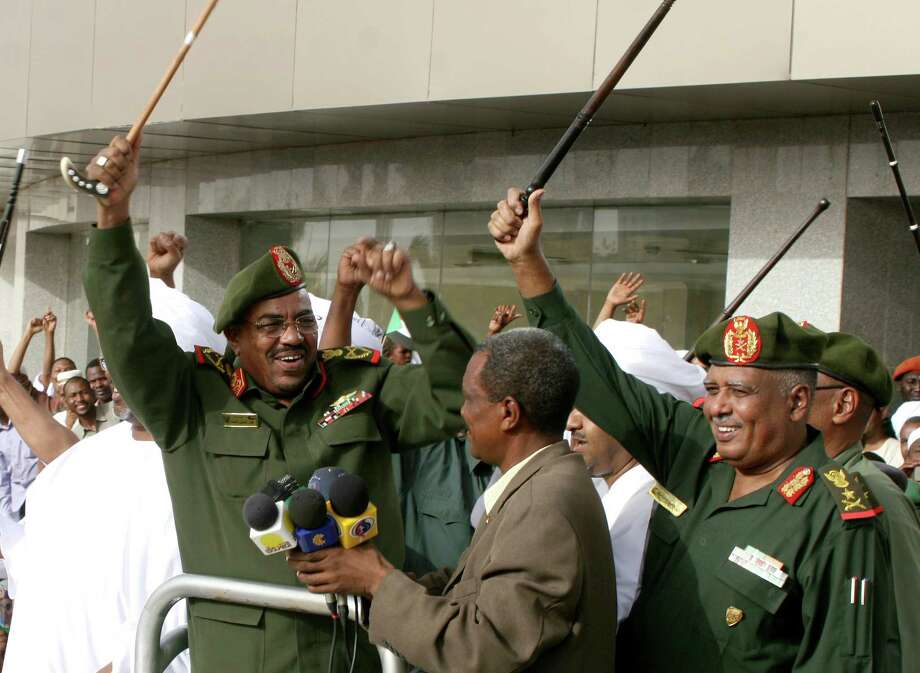 Sudanese President Omar al-Bashir, left, celebrates in Khartoum Friday following claims Sudanese forces drove South Sudanese troops out of a contested town. Photo: Abd Raouf / AP