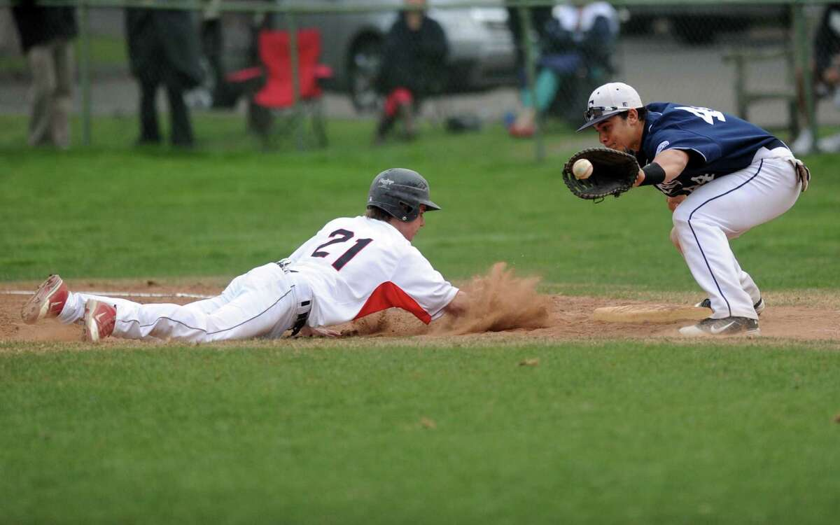 New Canaan's Grady Amrhein dives back to first base as Staples' Michael Terzian reaches for the ball during Friday's game at Mead Park in New Canaan on April 20, 2012.