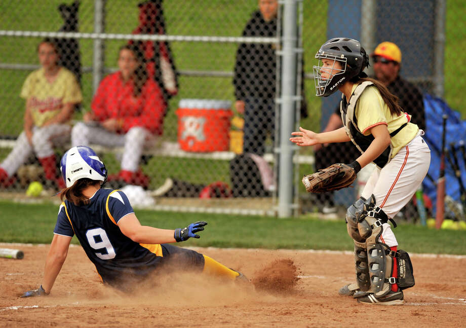 Brookfield's Angelina Pollen slides safe into home as Stratford catcher Melanie Cordero looks for the throw during their game at Brookfield High School on Friday, April 20, 2012. Brookfield won 17-0 in five innings. Photo: Jason Rearick / The News-Times