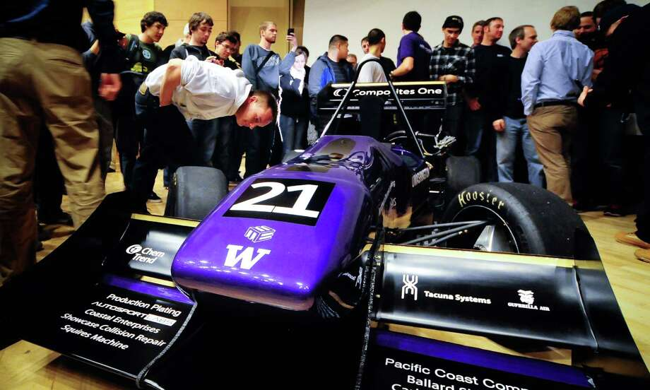 Members of the team and other interested observers take a look at the University of Washington's 2012 Formula motorsports car at Kane Hall on campus on Thursday, April 19, 2012. About fifty UW students from the mechanical engineering department's Formula SAE Team put in over 15,000 hours of work to build the car from scratch. Photo: LINDSEY WASSON / SEATTLEPI.COM