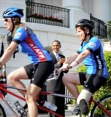 President Barack Obama cheers on bicyclists from the Wounded Warrior Project's Soldier Ride as they ride around the White House on Friday. Photo: Olivier Douliery / Abaca Press