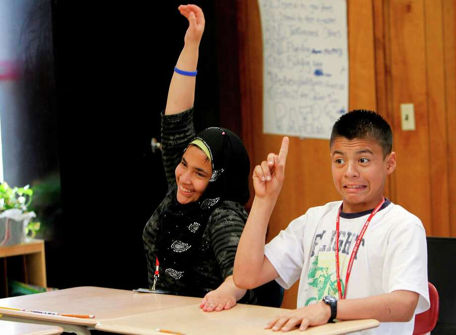 Razqia Al Tuma, from Iraq, and Brayan Rodriguez, from Honduras, compete to answer a question during a vocabulary lesson in the 'self-contained' class at Las Americas Middle School on Thursday, April 12, 2012, in southwest Houston.  The self contained class is an elementary style class that helps students acclimate to the U.S. school system for those who have never been to school in their own country  or have significant gaps in their schooling. Photo: Mayra Beltran, Houston Chronicle / © 2012 Houston Chronicle