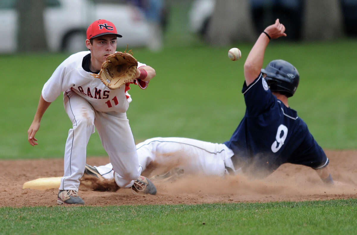 Staples' Elias Andrew slides safely into second as New Canaan's Doug Reilly reaches for the ball during Friday's game at Mead Park in New Canaan on April 20, 2012.