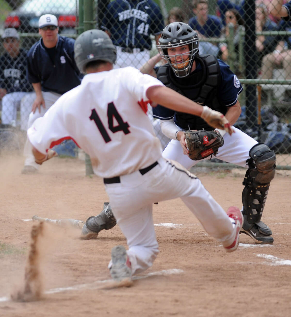New Canaan's Gordon Jones slides to home plate as Staples catcher James Frusciante tags hime out during Friday's game at Mead Park in New Canaan on April 20, 2012.