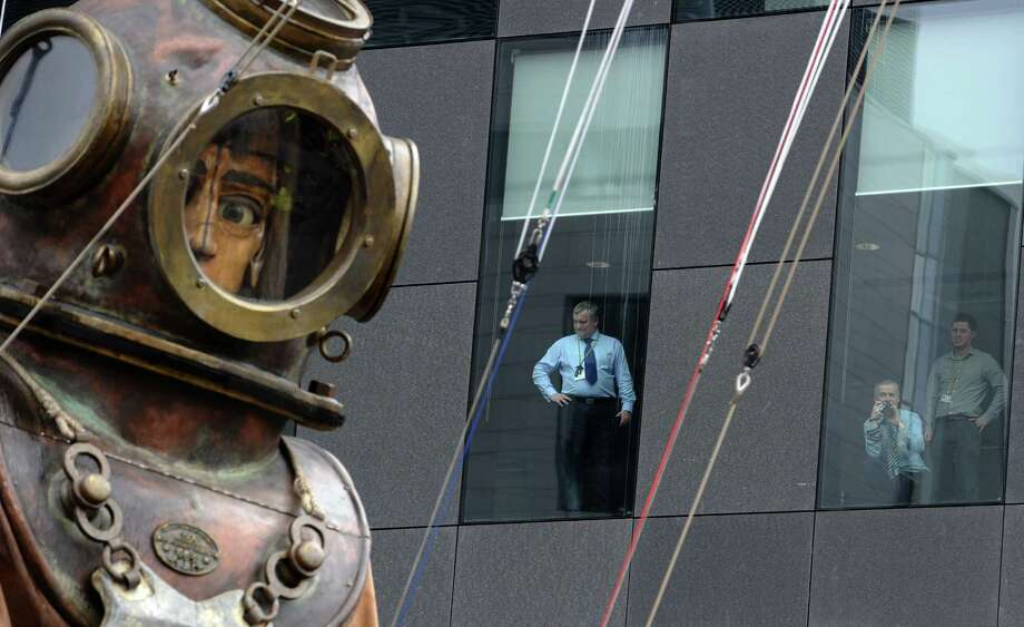 "People look out of their windows to watch a giant deep sea diver puppet, part of a street theatre production entitled ""Sea Odyssey"", walk through the streets in Liverpool in north-west England, on April 20, 2012.  Two puppets, a man and a girl, his niece, will roam through the city's streets looking for each other during the three day production. Photo: PAUL ELLIS, AFP/Getty Images / AFP"