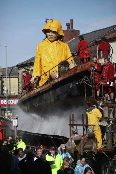 The Little Girl Giant Marionette makes it's way through the streets of Liverpool as the Titanic Sea