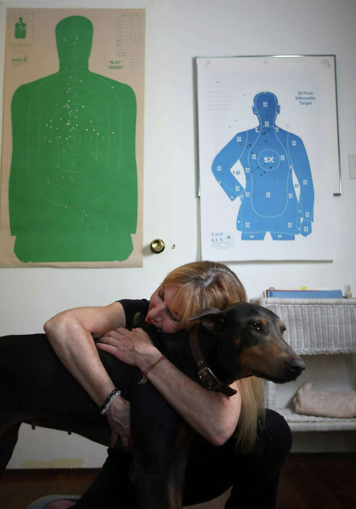 Geffin hugs her new dog in her home. Behind her are paper silhouettes she has used for target practice.