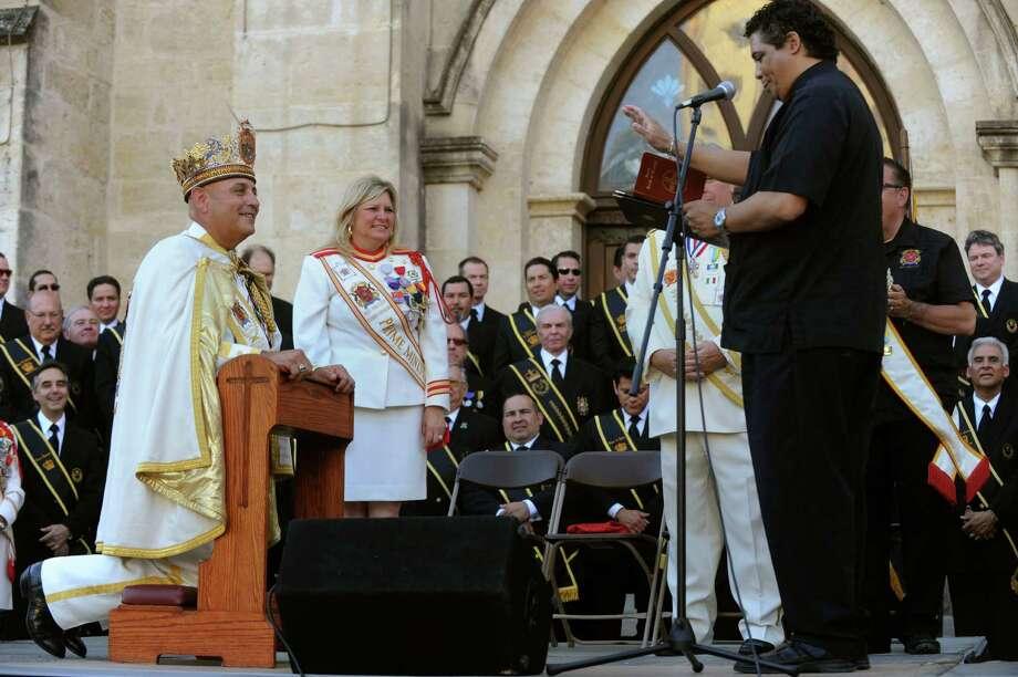 Father Tony Vilano, right, blesses Rey Feo LXIV, Richard Ojeda, during his coronation ceremony in Main Plaza on Friday, April 20, 2012. Photo: BILLY CALZADA, SAN ANTONIO EXPRESS-NEWS / San Antonio Express-News