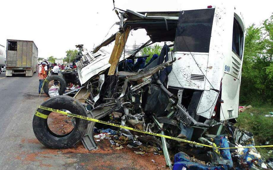 Wreckage of a bus that carried up to 70 people was strewn along a highway in Veracruz state after one of the trailers pulled by a big rig slammed into the private bus early Friday, killing at least 43 people. The driver of the rig fled the scene. Photo: SERGIO HERNANDEZ / AFP